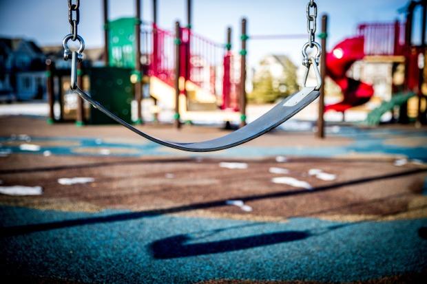 Balançoire souple devant une aire de jeux pour enfants